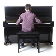 Teenage boy sits at upright piano in studio Stock Photos