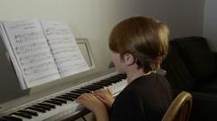 Happy cute boy plays piano - stock footage
