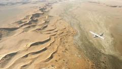 Aerial of Namibia Desert, a small plane in focus flying over it Stock Footage