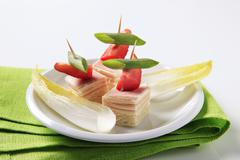 Ham and cheese canapes and endive leaves Stock Photos