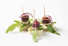 Anchovy canapes garnished with arugula and onion Stock Photos