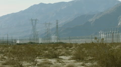WINDMILLS SURROUNDING ELECTRICAL TOWERS Stock Footage