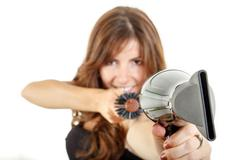 Pretty hairstylist holding hairdryer and hairbrush Stock Photos