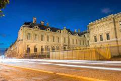 car light trails across paris avenues at night - stock photo