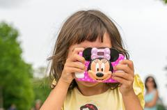 Paris, france - july 20, 2014: baby girl enjoy city view with her toy camera. Stock Photos
