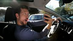 Crazy man doing selfie with cell phone while driving Stock Footage