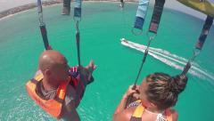 A happy couple parasailing behind a boat - stock footage