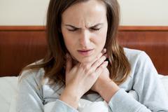 Woman having a sore throat Stock Photos
