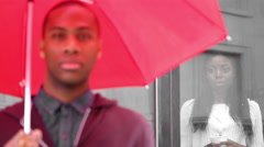A man holding a red umbrella stands in front of a window - stock footage
