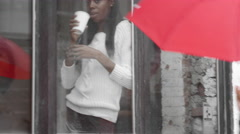 Woman behind a glass window drinks tea while a man with an umbrella walks by - stock footage