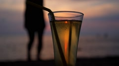 Female Silhouette and Glass of Refreshing Beverage at Sunset Stock Footage