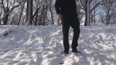 Headless shot man in black suit get down from snowy hill, winter epic landscape - stock footage