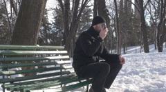 Man answer mobile phone, talking, siting alone in park on bench, play with snow Stock Footage