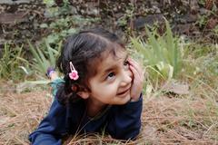naughty little girl lying on grass. - stock photo