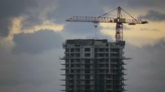 Crane on site on overcast sky background Stock Footage