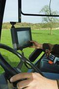 technical equipment aboard a tractor, a hand touching a touch screen. - stock photo