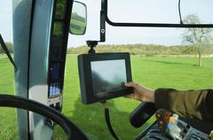 Stock Photo of technical equipment aboard a tractor, a hand touching a touch screen.