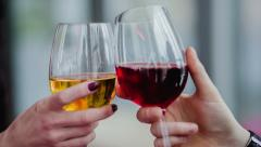 Glasses of white and red wine clink Stock Footage