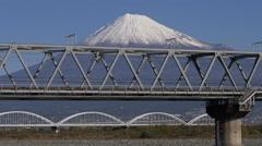 Shinkansen Train Crosses Fujikawa near Mount Fuji in Japan Stock Footage