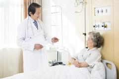 Doctor with patient in hospital - stock photo
