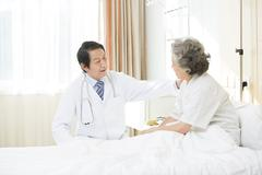 Doctor talking with patient in hospital - stock photo