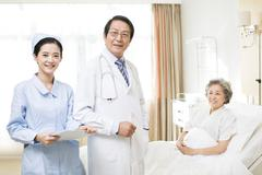 Medical workers with patient in hospital Stock Photos