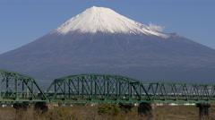 Tokaido Line Local Train Crosses Fujikawa near Mount Fuji Stock Footage