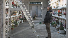 Man with a bunch of flowers at cemetery Stock Footage
