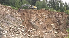 Excavator working on the edge of a granite quarry wall Stock Footage