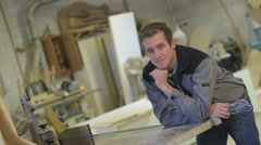 Student in carpentry leaning on workbench Stock Footage