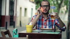 Man talking on cellphone, drinking beer and eating snack in cafe HD Stock Footage