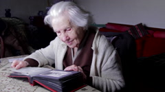 Stock Video Footage of 99 Years Old Woman Looking At A Photo In An Old Photo Album, Memories, Nostalgia