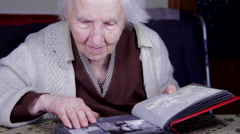 Stock Video Footage of 99 Years Old Woman Putting Photos In An Old Photo Album, Memories, Senescence