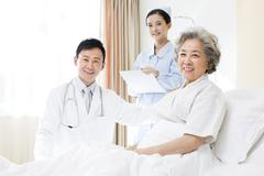 Medical workers with patient in hospital - stock photo