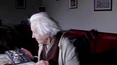 99 Years Old Woman Sitting At Table And Flipping Through An Old Photo Album, Pan - stock footage