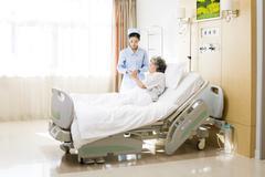 Nurse taking care of senior woman in hospital - stock photo