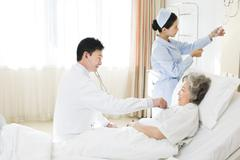 Doctor using stethoscope on patient in hospital - stock photo