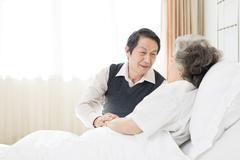 Senior man taking care of wife in hospital - stock photo