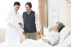 Doctor with senior couple in hospital Stock Photos