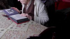 99 Years Old Woman Sitting At Table And Flipping Through An Old Photo Album Tilt - stock footage