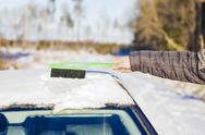 Stock Photo of Man cleans with brush the car out of the snow