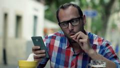 Man using smartphone, drinking beer and eating snack in cafe HD - stock footage