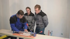 teacher with students using ceramic saw - stock footage