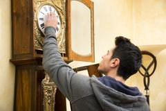 Young man checking a pendulum and winding the mechanism - stock photo