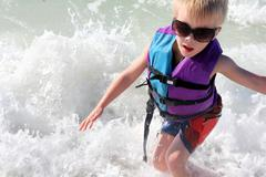 Young child playing in ocean waves in life jacket Stock Photos