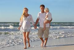 Happy family of three people walking on beach along ocean Stock Photos