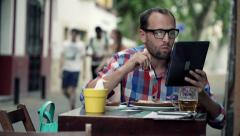 Young man with tablet computer eating tortilla, sitting in cafe in city HD Stock Footage