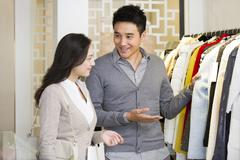Clothing store owner recommending clothes to customer Stock Photos