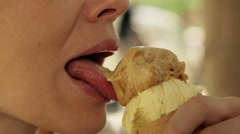 Close up of woman eating and licking ice cream in city HD Stock Footage