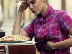 Young woman gets stomach ache during lunch in cafe NTSC Stock Footage